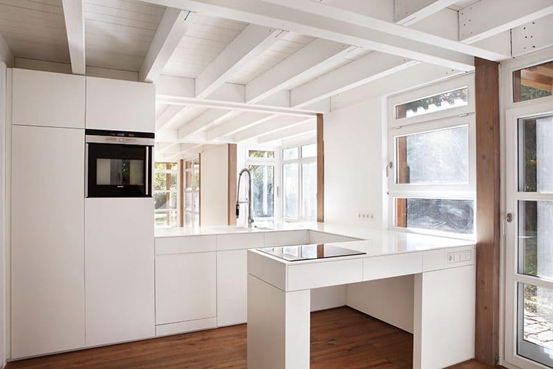 Einbauküche mit Front aus Mineralwerkstoff. Weiß lackiert.