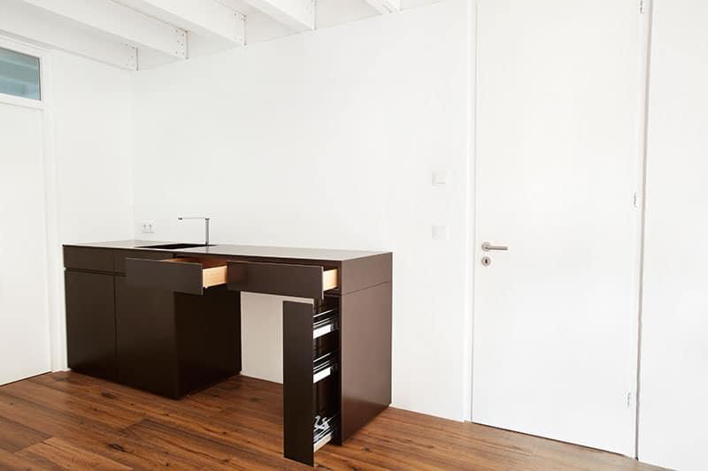 Barmöbel aus Mineralwerkstoff mit integrierter Spüle und Minikühlschrank.