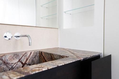 Waschtisch aus Naturstein, flächenbündiger Spiegelschrank.